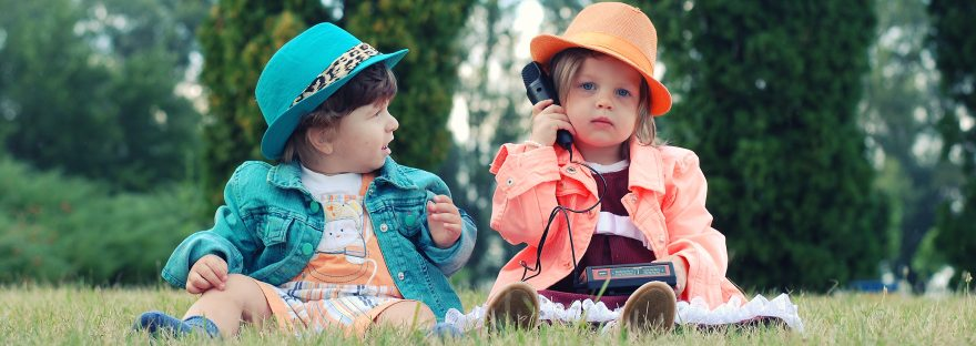 Two kids sitting in a field with a phone pretending to be adults