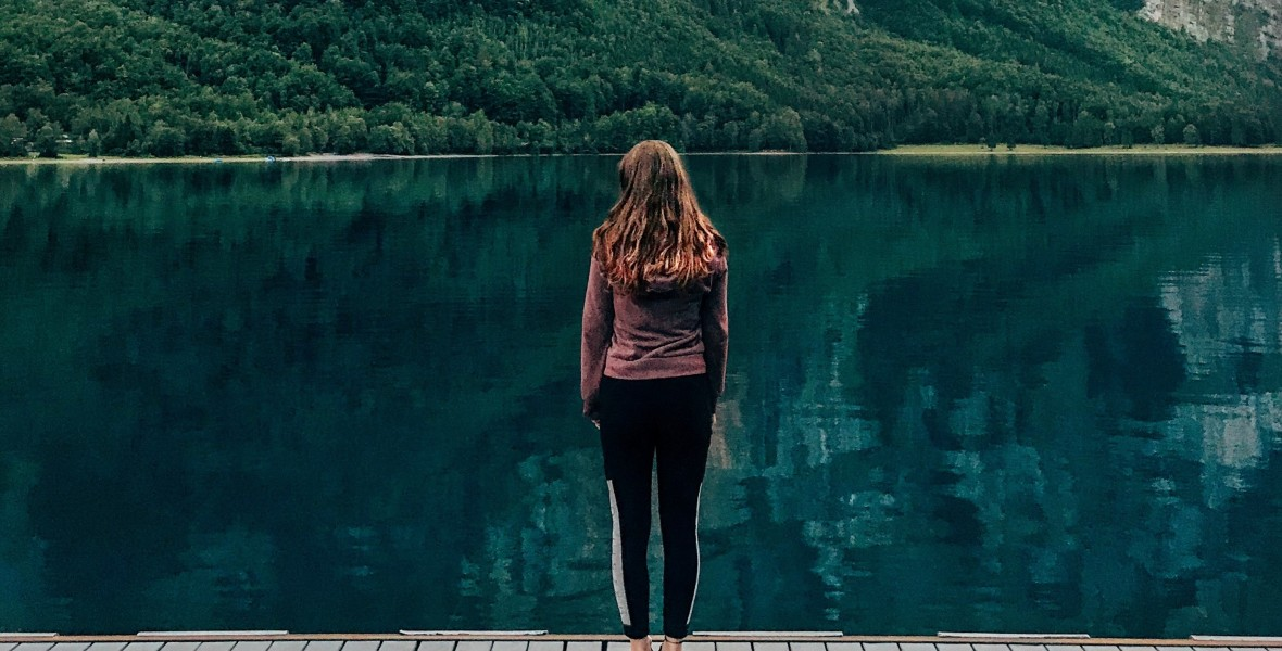 Young woman standing on a dock on a lake looking out at trees on a cliff face.