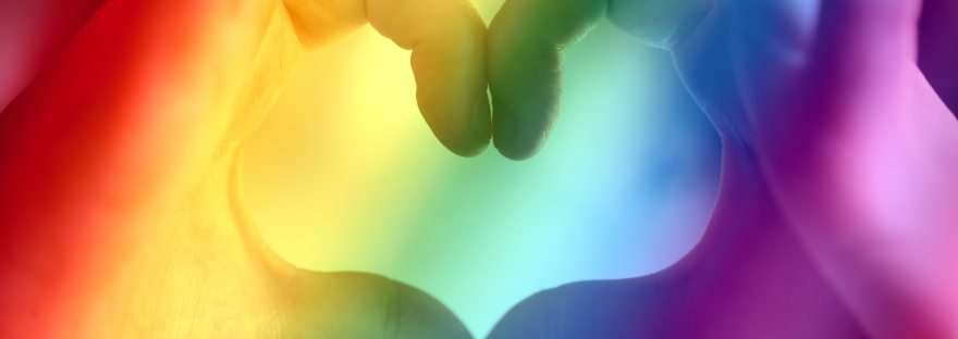 Hands in the shape of a heart with a rainbow filter for Pride month.