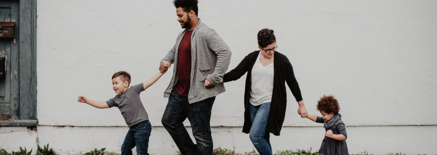 Family of four holding hands and walking in the rain