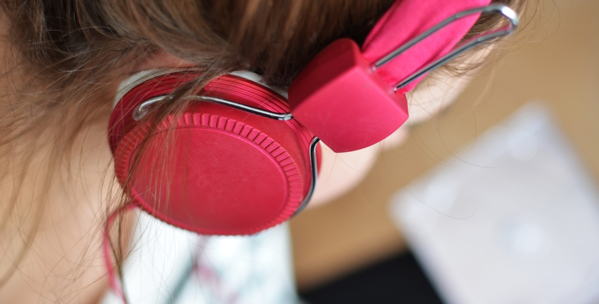 Woman wearing pink headphones and a white shirt