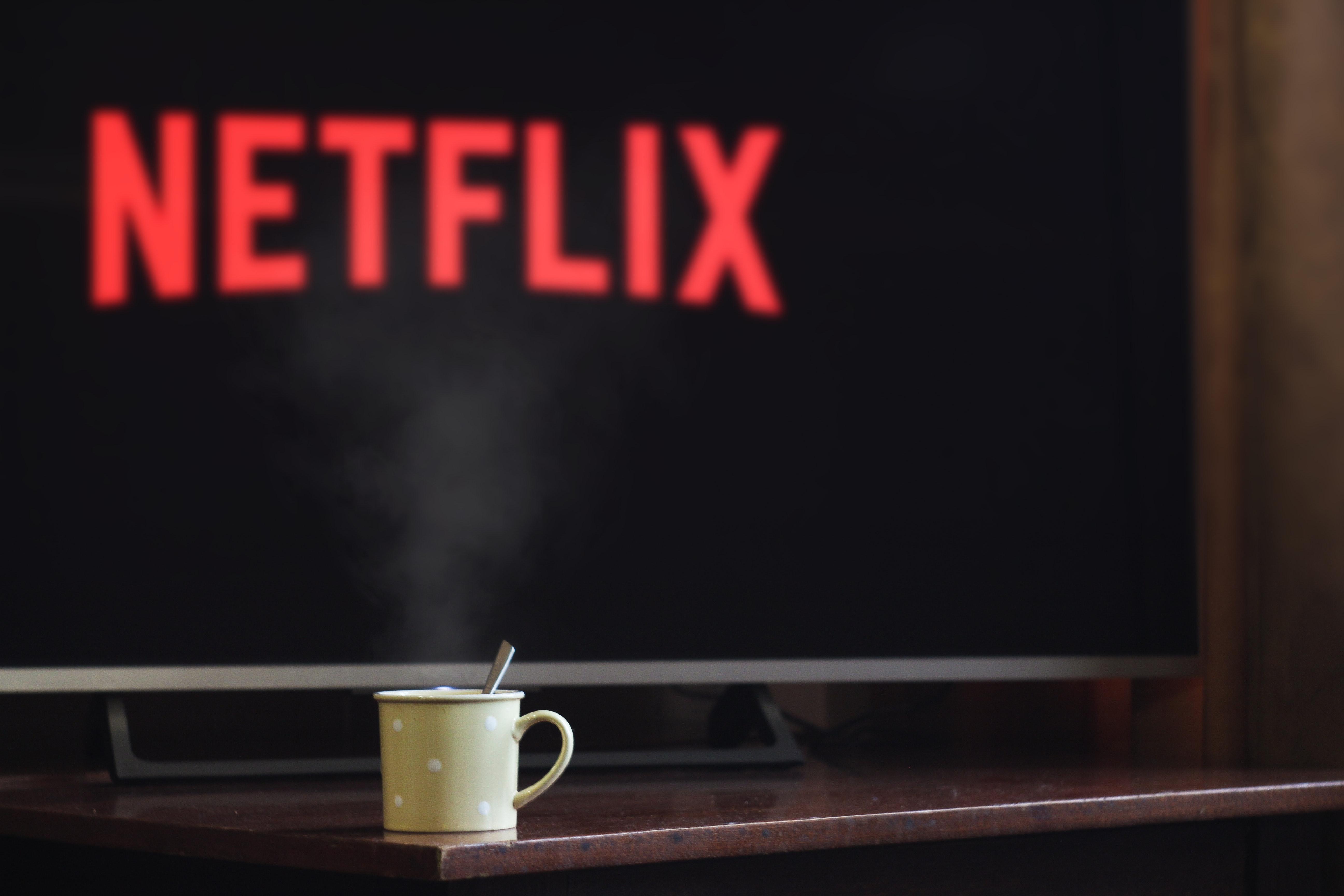 Netflix on TV with a coffee mug