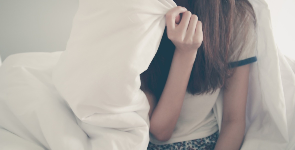 Girl with long hair hiding behind big white blanket